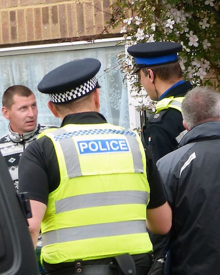 Officers speak to one of the migrant workers who lives at the house in Friday Bridge.