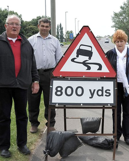Councillors, from left, Kit Owen, Rob Skoulding and Jan French, with one of the roadworks signs left