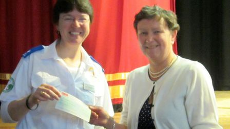 Ely Flower Club annual show.Chairman, Grace Bent presenting a cheque to Lisa Chapman, from CamSAR.