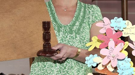 Lesley Wright displays a board and wooden candlestick, along with an arrangment she had made.