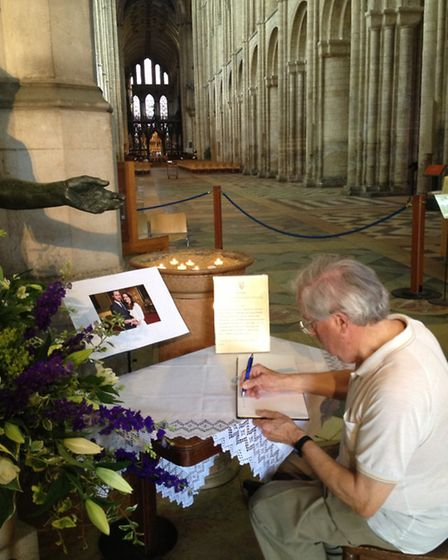 A cathedral visitor signs the book of congratulations for the Duke and Duchess of Cambridge.