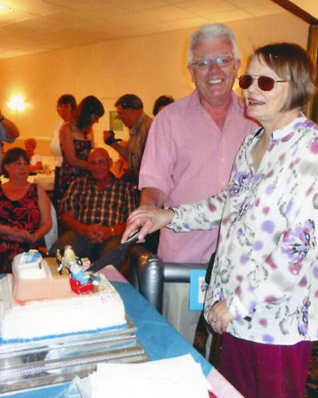 David and Pauleen McCullagh cut a cake at their leaving party.