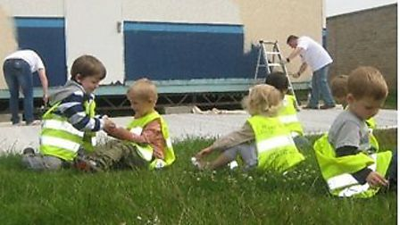 Children play in the garden while the helpers are hard at work