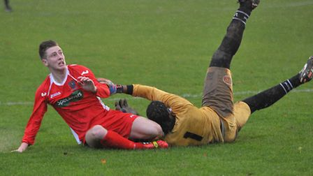 James Tricks collides with the Long Buckby goalkeeper. Football. Picture: Steve Williams.