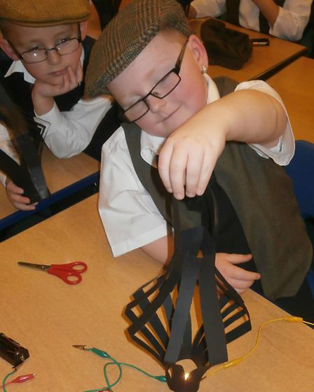 A pupil gets to work on a lamp.