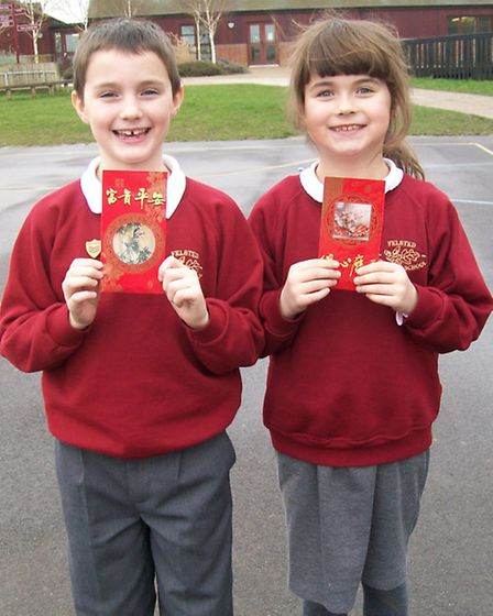 Dylan and Olivia, both aged nine, show off their lucky red purses which they were given by Shivon.