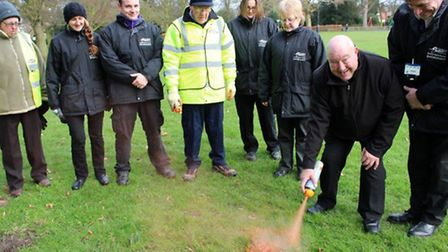 Cllr Peter Murphy sprays some dog poo in Wisbech Park, watched by council officers.