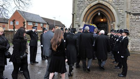 Police form a guard of honour as the coffin is carried into the church, followed by relatives of Jon