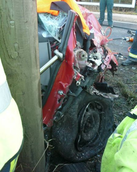 Firefighters work to free a casualty from a car following a collision on the A142 near Mepal