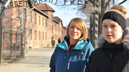 Teachers Heather Carter, left, and Meredith Jewson at the entrance to Auschwitz I. The sign says: Ar