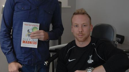Rene Schellekens (left) with personal trainer Blake Newbold and a copy of the book.