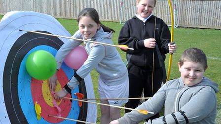 Enrichment day at Burrowmoor School, March. Left: Leah, Scarlet and Alex has a go with the archery s