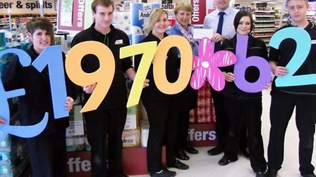 Chris Wright, store manager, back right, presenting the cheque to Karen Roberts, area manager at CLI