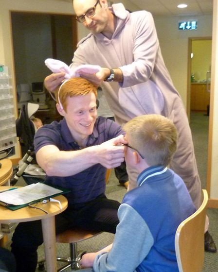 Elliott James receives his new glasses from dispensing consultant James Burden, watched by the 'East