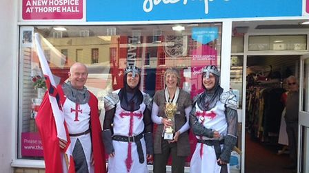 Sue Ryder staff are presented with a trophy by members of the Royal Society of St George.
