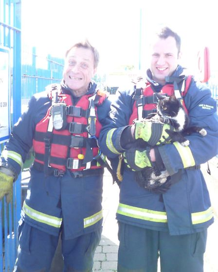 Two firefighters with the rescued cat. Picture: CAMBS FIRE AND RESCUE