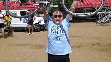 Peter Bryant celebrates completing his charity cycle ride.