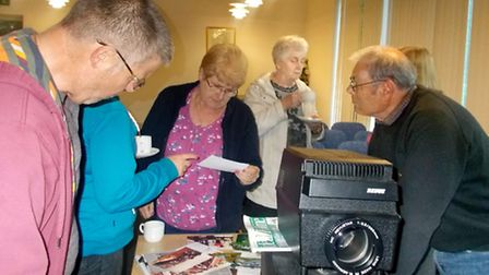 March Society members look at the old newspaper cuttings and photographs.