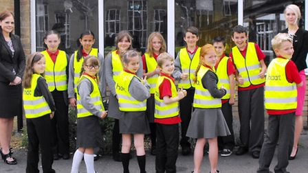 Children show off their high visibility jackets.