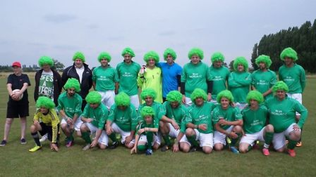 Macmillan FC players gather for their team photo sporting colourful wigs.