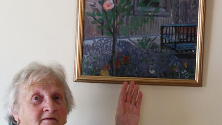 Brenda Bullen shows off the painting she donated to the tea room.