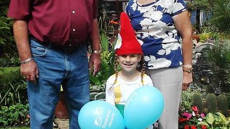 Ede Jackson, aged 6 welcoming visitors, dressed as an elf, patiently sitting on a toadstool in her g