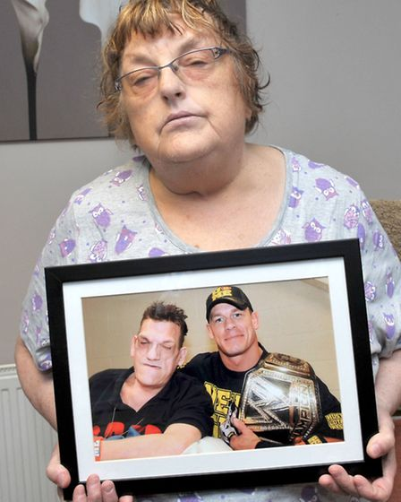 Rita Smith with a framed picture of her son Robert with WWE wrestler John Cena, taken last year in N
