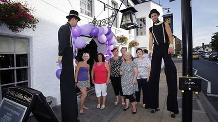Customers with stilt walkers outside the entrance