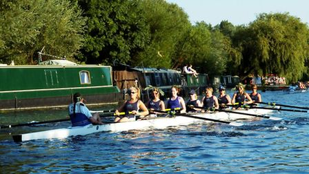 Isle of Ely women's crew rowing back home wearing the traditional willow branches signifying they ha