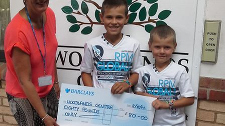 Woodlands lead nurse Lynda Hall receives a cheque from (from left) Riley and Keaton Astley.