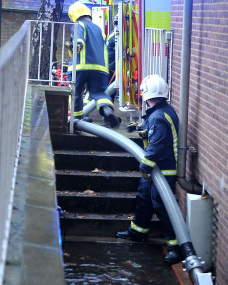 Firefighters pump water out of the police station. Picture: Steve Williams.