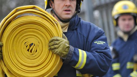 Firefighter laying out hose reel