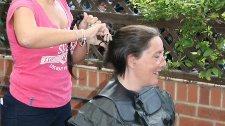 Hairdresser Rachel Fearing cuts off Rebecca Andrew's 18-inch plait, which she has donated to the Lit