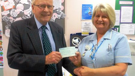 Ron Williams, preceptor for the Freemasons presenting Lorna Lombardo with a cheque for £300.