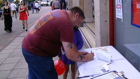 A member of public signs the petition.