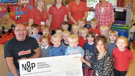 Roland Burton Hands over a cheque to Murrow Pre-school, with proceeds from a magazine article about