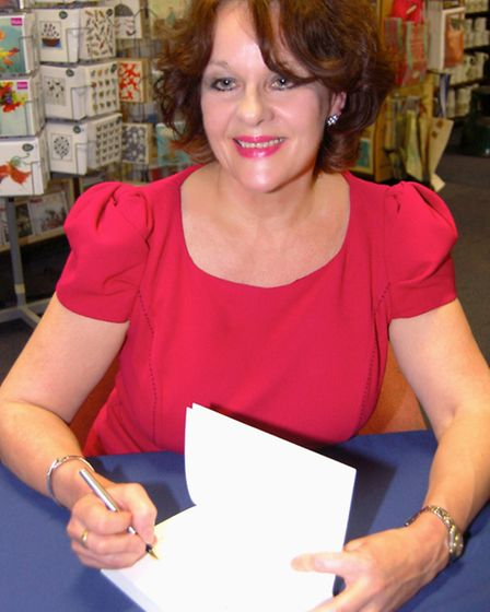 Author Ellee Seymour signs a copy of her book Shop Girls