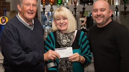 Seniors' club captain Trevor Sewell presenting Marilyn Bishop with a cheque.