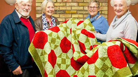 John and Pat Simpson on the left receiving the quilt, with Joan Batten in the blue and Cecilia Lawso