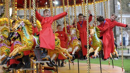 Choristers enjoy a ride on a vintage carousel at the Ely Cathedral Christmas Gift & Food Fair.