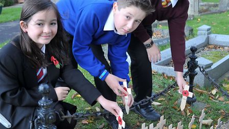 Past and present Thomas Eaton pupils laying wooden crosses at the war memorial in St Peter's Church