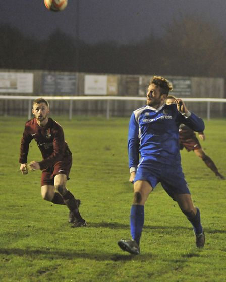 An Ely City player looks on as a Kirkley player gets ready to head the ball.