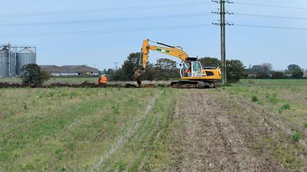 Digger and workers in the field next to Estover for excavation work.