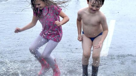 Two children play in the rain on the day of the March floods.