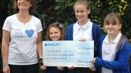 Shirley Gower (founder of the charity) being presented with the cheque from school by Olivia Roberts