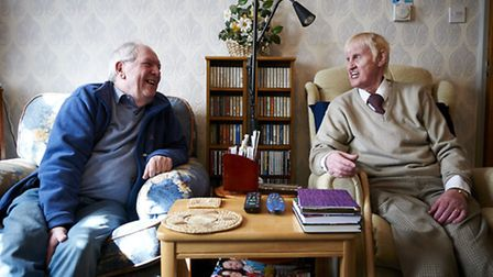 A Care Network volunteer shares a joke with one of his clients