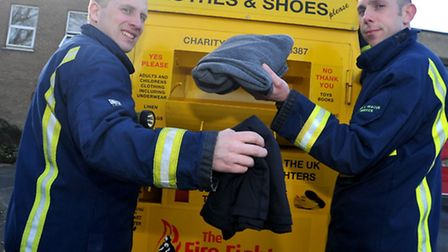 Watch commander Rob Cowling and firefighter Matt Woodcock donate clothes into the FFC bank.