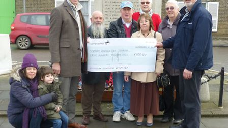 Hamish Ross, third left, chair of the detecting society, hands the funds over to Charles Warner of t
