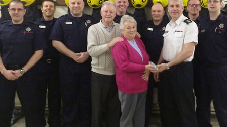 Gary and Lynn Boon hand over cheque to watch commander Clive Allen, with his Littleport crew.
