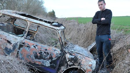 Dean James with his burnt out Mini. Picture: Steve Williams.